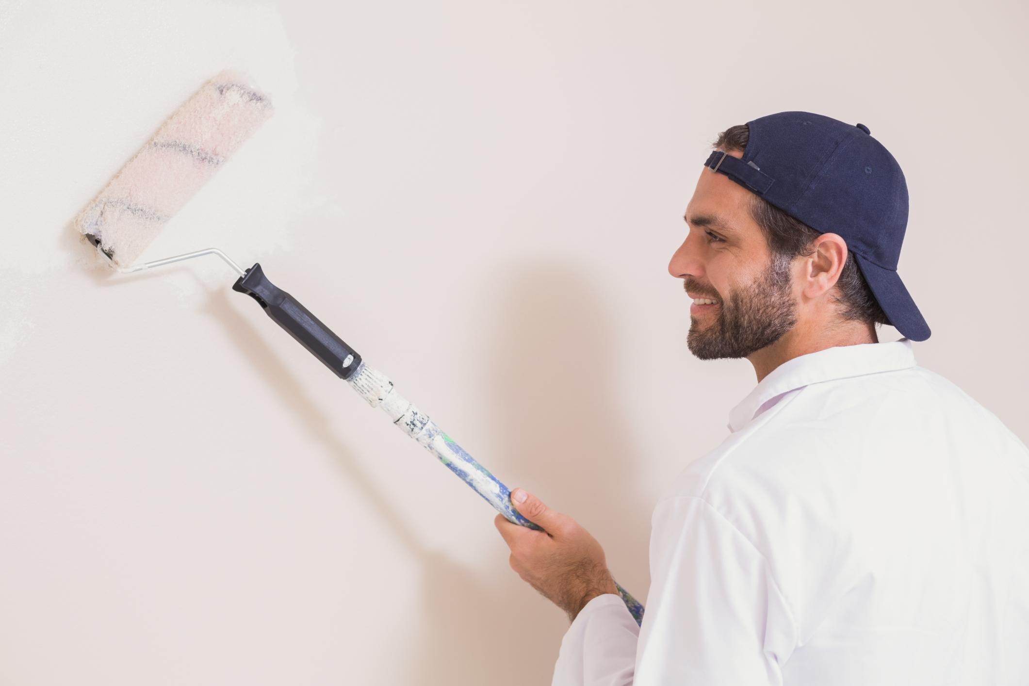 man happily painting the wall