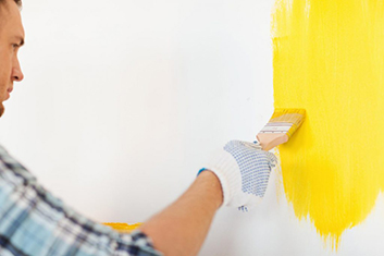 man painting the wall yellow